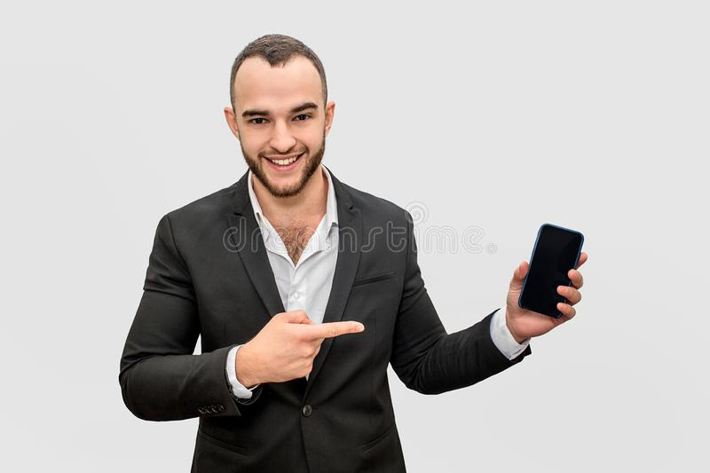 Happy businessman points on phone. He holds it in hand. Young man look on camera and smile. Isolated on white background. royalty free stock photography