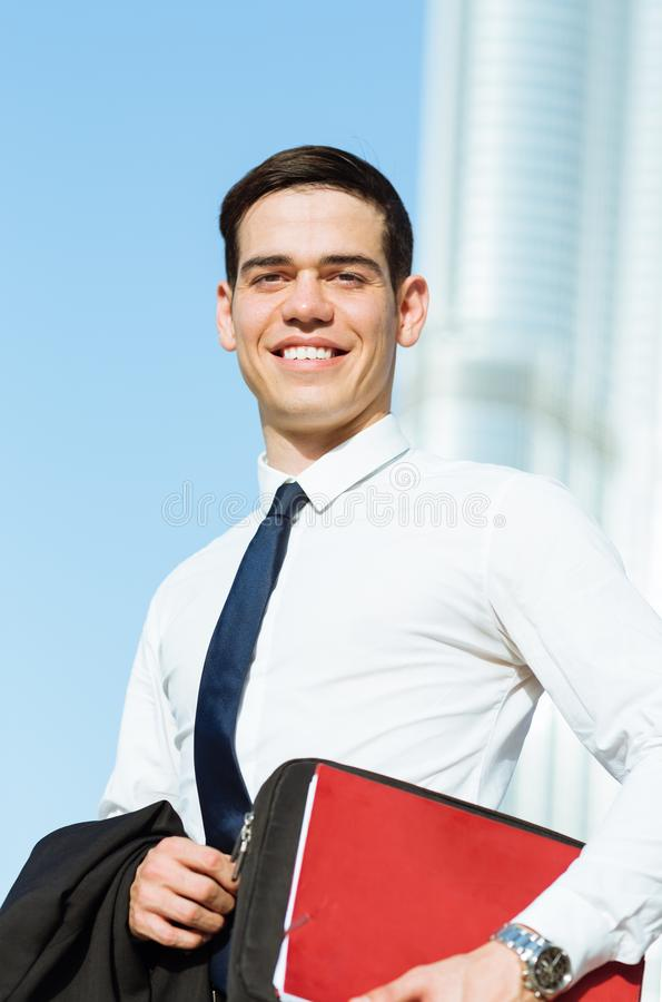 Happy businessman portrait with a modern city background. stock photography
