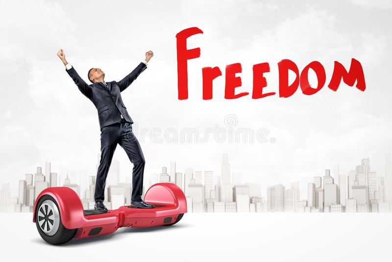 Happy businessman raising arms on red hoverboard with `Freedom` sign on white city skyscrapers background royalty free stock photo