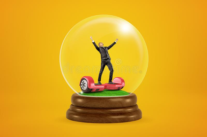 Happy businessman raising arms on red hoverboard in a snow globe on yellow background royalty free stock image