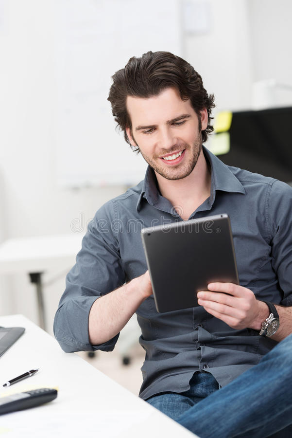 Happy businessman reading his tablet screen royalty free stock photos