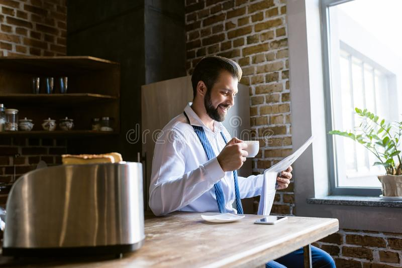 Happy businessman reading newspaper and drinking coffee at kitchen. In morning royalty free stock image