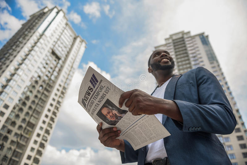 Happy businessman reading newspaper outdoors. Cheerful man wants to know news in city. He is standing and holding paper. Man is looking around with satisfaction royalty free stock image