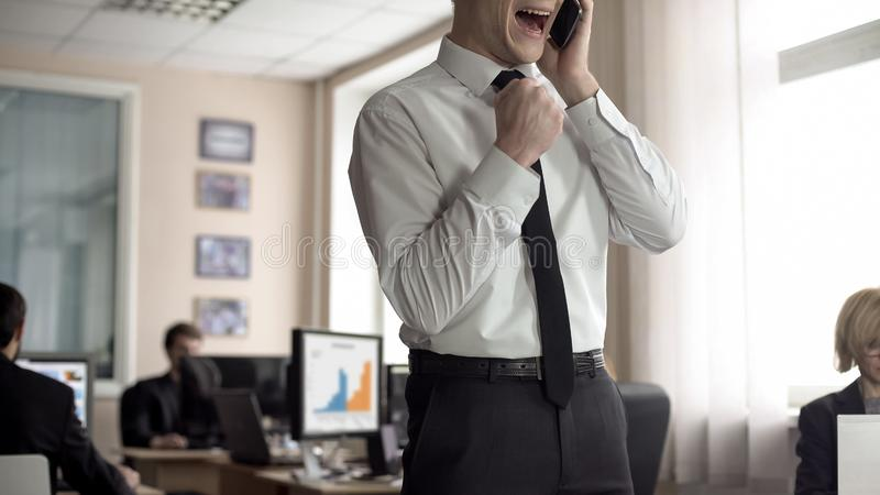 Happy businessman receiving good news on phone, successful company prosperity. Stock photo stock photos