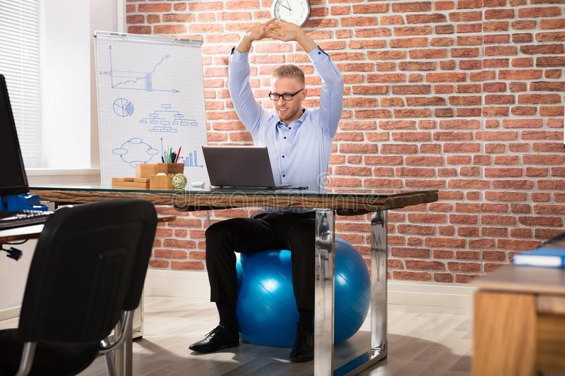 Happy Businessman Relaxing On Fitness Ball In Office. Close-up Of A Happy Businessman Relaxing On Fitness Ball In Office stock photography