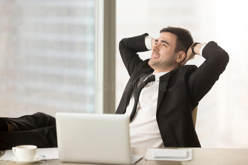 Happy businessman relaxing hands behind head near laptop, job do. Happy relaxed businessman resting hands behind head near pc laptop looking away sitting at stock photo