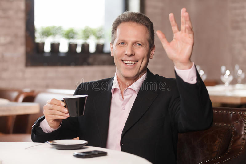 Happy businessman at restaurant. Cheerful businessman drinking c stock image