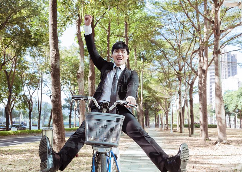 Happy Businessman riding bicycle to work on urban street royalty free stock image