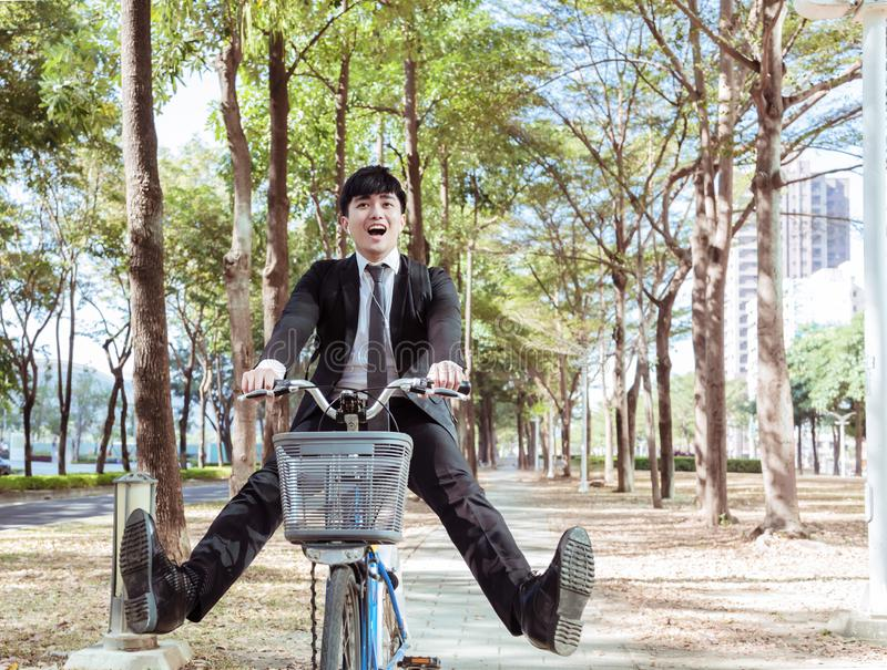 Happy Businessman riding bicycle to work on urban street stock photo