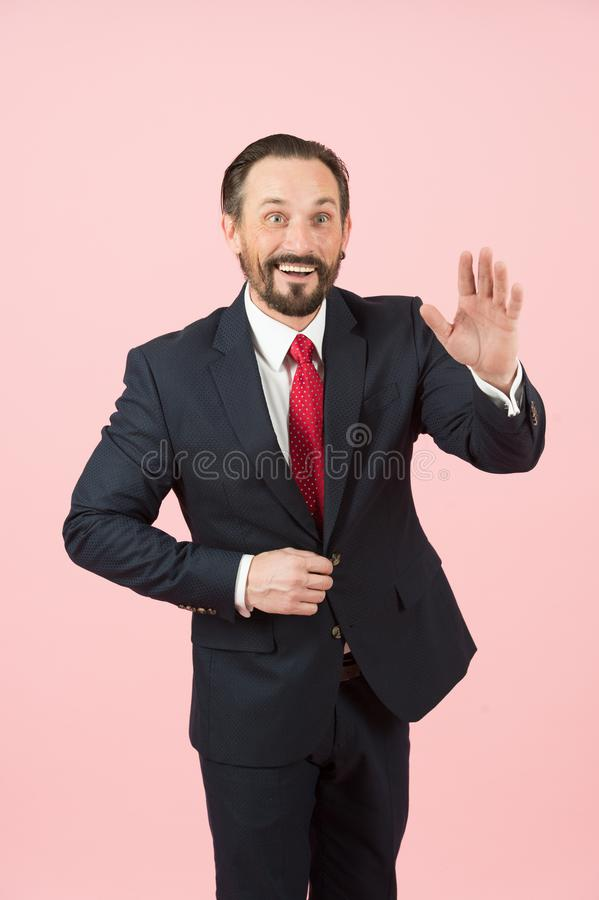 Happy businessman saluting on pastel pink background. A handsome businessman is greeting or saying hello his partners. Happy and smiled businessman saluting on royalty free stock photo