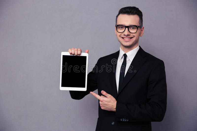 Happy businessman showing blank tablet computer screen. Portrait of a happy businessman showing blank tablet computer screen over gray background royalty free stock photos