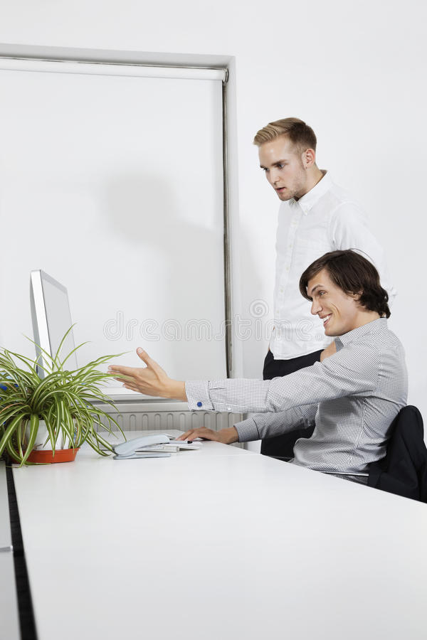 Download Happy Businessman Showing Computer Screen To Coworker At Desk Stock Photo - Image: 30855488