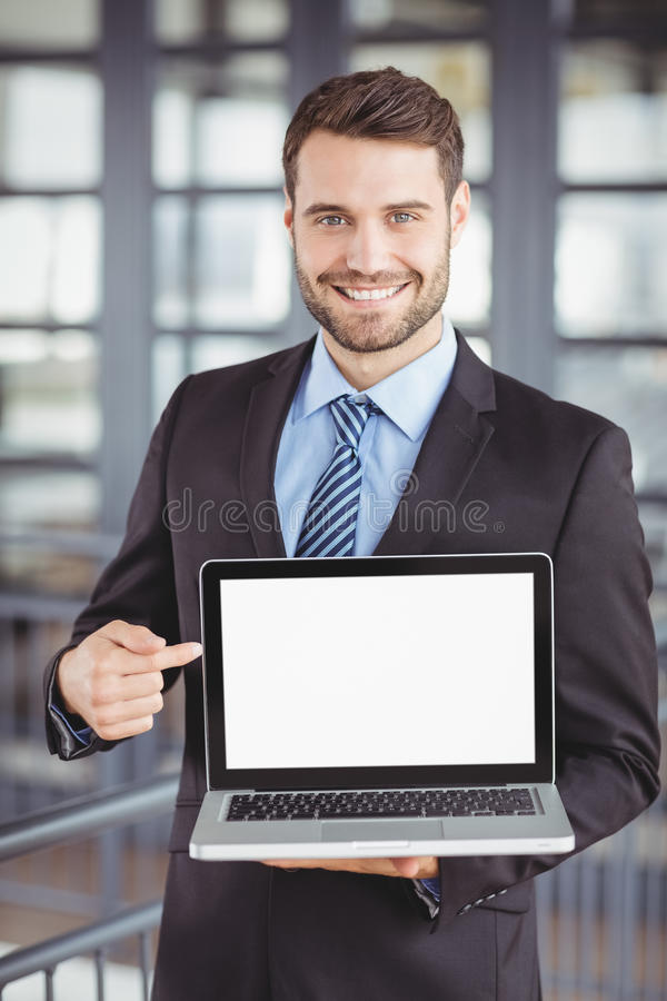 Happy businessman showing laptop. Portrait of happy businessman showing laptop while standing in office royalty free stock images