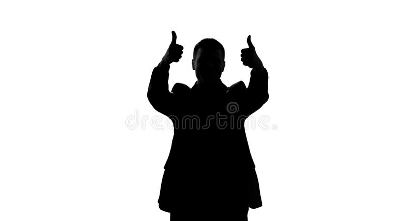 Happy businessman silhouette showing thumbs up, success, great achievement stock photo