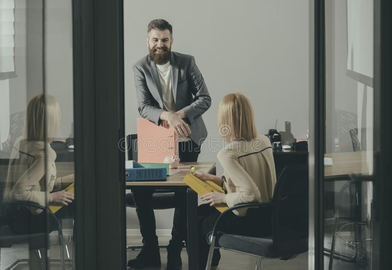Happy businessman smile at businesswoman in office. Bearded man and woman discuss financial report. Boss and secretary stock photos
