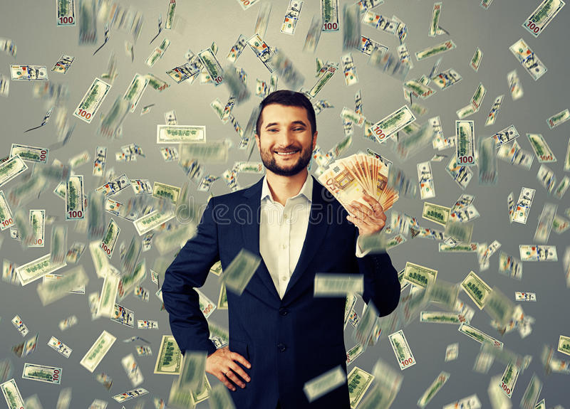 Happy businessman standing under money rain stock images