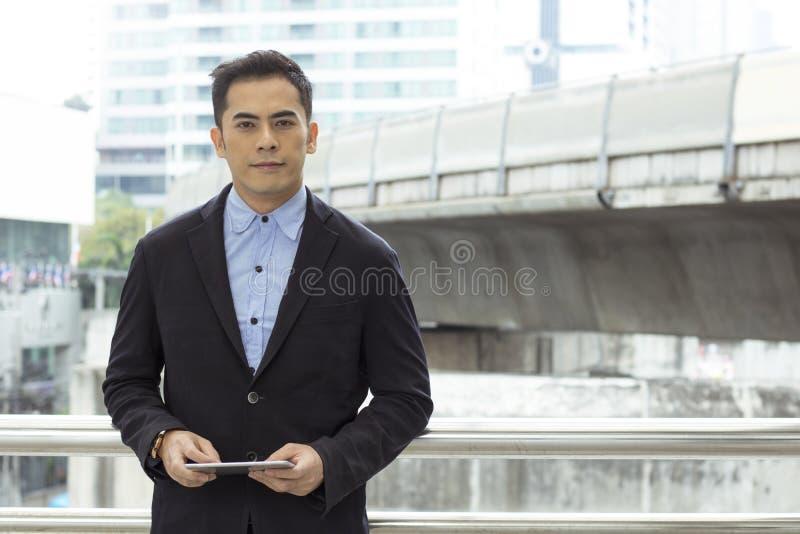 Happy businessman standing on walkway of building stock image