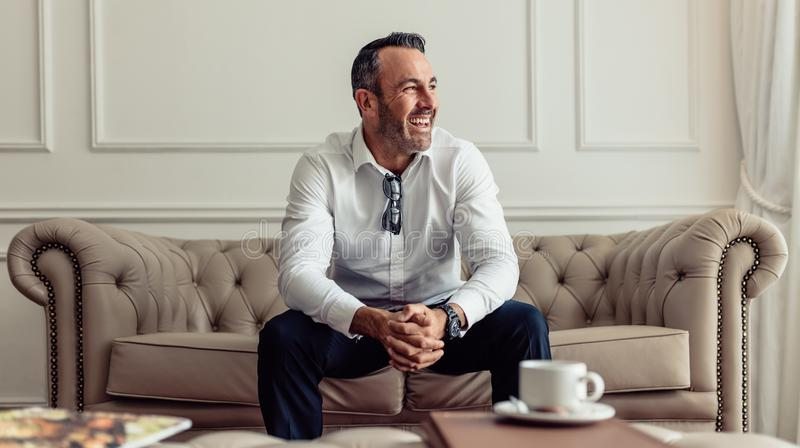 Happy Businessman staying in a hotel room. Portrait of cheerful businessman sitting on sofa in hotel room and looking away laughing. CEO staying in luxurious stock photos