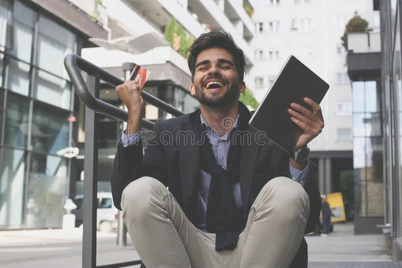 Businessman on street using credit card and iPod and rece royalty free stock photography