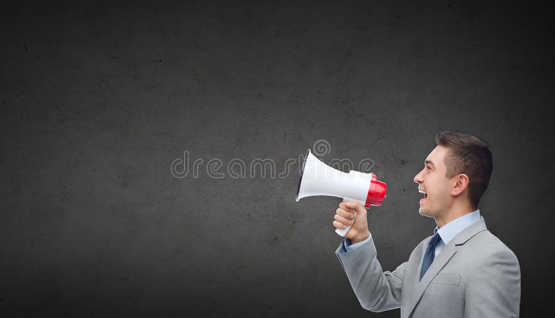 Happy businessman in suit speaking to megaphone stock image