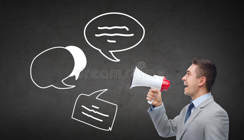 Happy businessman in suit speaking to megaphone royalty free stock image