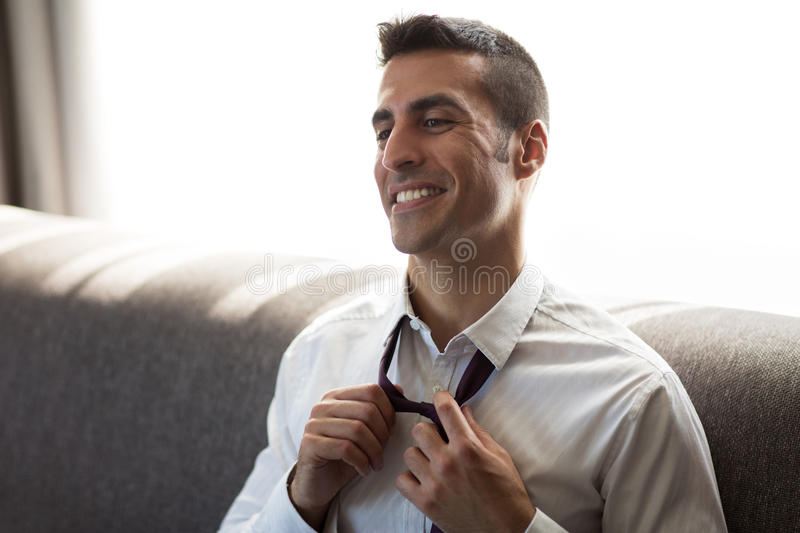 Happy businessman taking off his tie at hotel room. People concept - happy smiling businessman taking off his tie at hotel room stock images