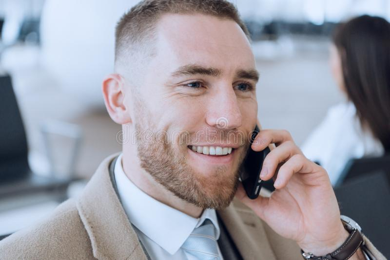 Happy businessman talking on cellphone at the airport waiting lounge. Handsome caucasian businessman at waiting room in stock photo