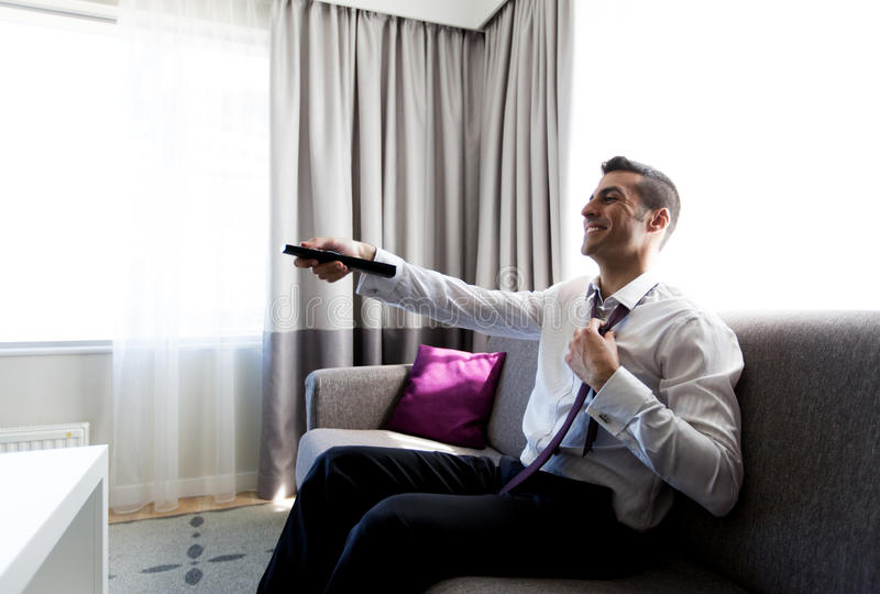 Happy businessman with tv remote at hotel room. People and rest concept - happy businessman with tv remote taking off his tie at hotel room stock photos