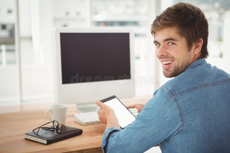 Happy businessman using digital tablet while sitting at desk royalty free stock images
