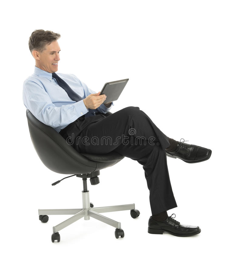 Happy Businessman Using Tablet Computer While Sitting On Office stock image