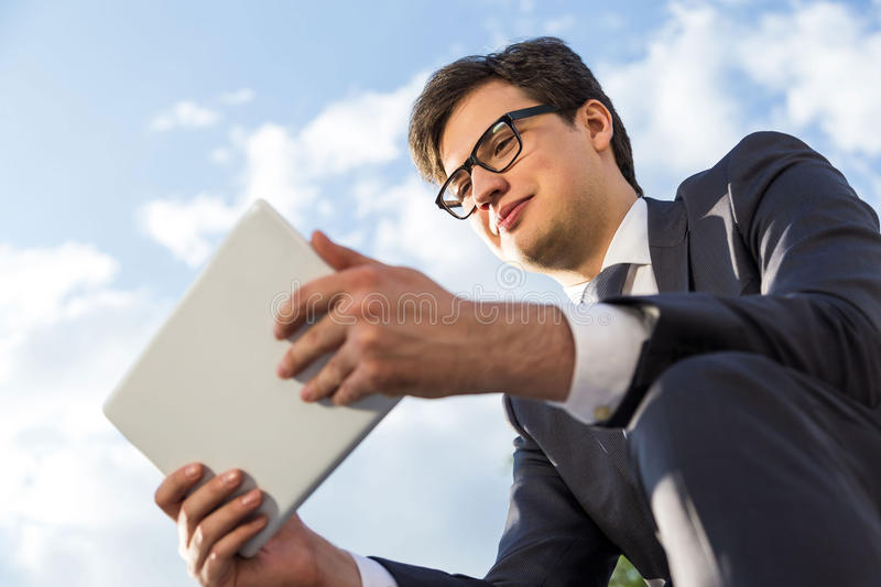 Happy businessman using tablet outside stock photos