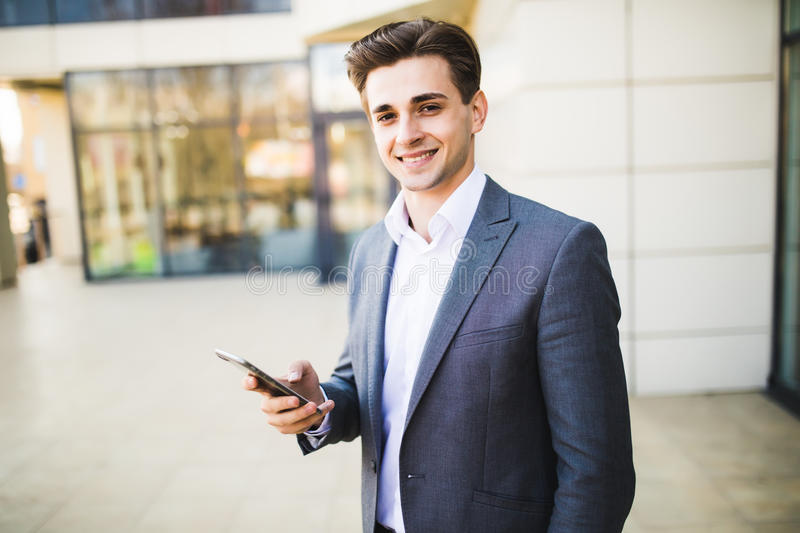 Happy businessman wearing suit and using modern smartphone near office. Happy smiling businessman wearing suit and using modern smartphone near office stock images