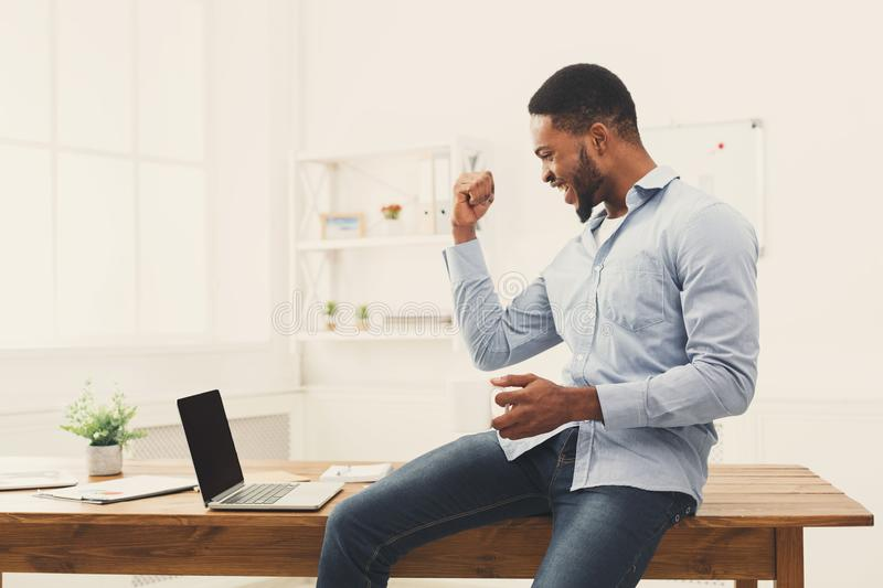Happy businessman win. Winner, black man in office. Happy excited businessman celebrate his success. Winner, black man in office reading on laptop, copy space stock images