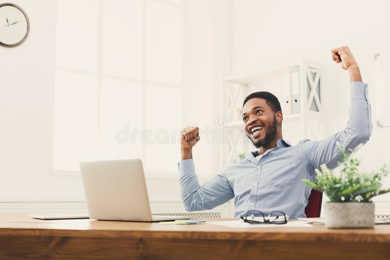 Happy businessman win. Winner, black man in office. Happy excited businessman celebrate his success. Winner, black man in office reading on laptop, copy space royalty free stock photography