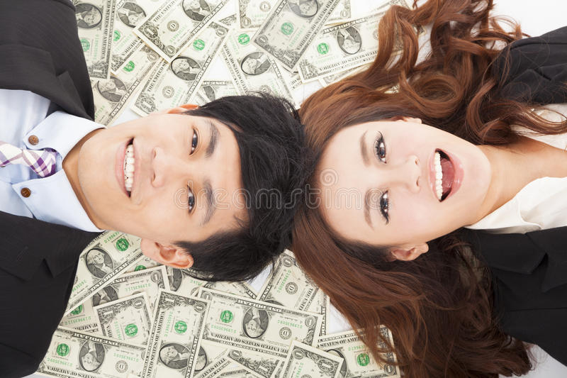 Happy businessman and woman lying on the money royalty free stock photo