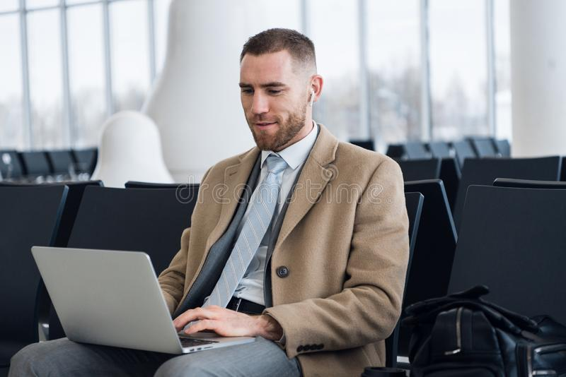 Happy businessman working on the laptop at the airport waiting lounge. Handsome caucasian businessman at waiting room in stock image