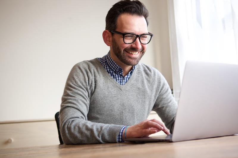 Happy businessman working with laptop computer. Portrait of happy businessman working with laptop computer stock photo