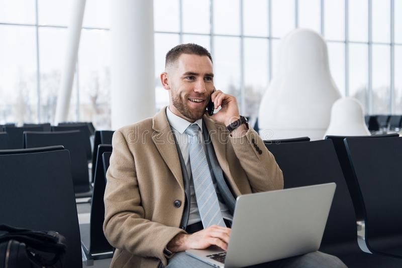 Happy businessman working on the laptop and talking on cellphone at the airport waiting lounge. Handsome caucasian royalty free stock photography