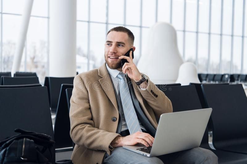 Happy businessman working on the laptop and talking on cellphone at the airport waiting lounge. Handsome caucasian royalty free stock photos