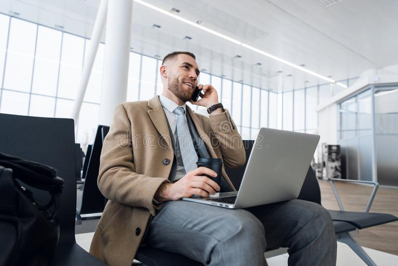 Happy businessman working on the laptop and talking on cellphone at the airport waiting lounge. Handsome caucasian royalty free stock image