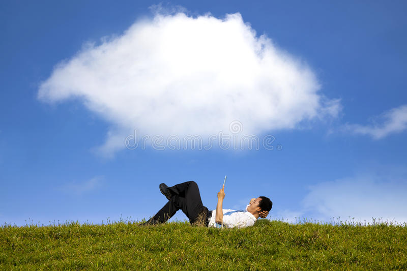 Happy businessman working with tablet pc. Cloud computing concept and happy businessman working with tablet pc on the green grass