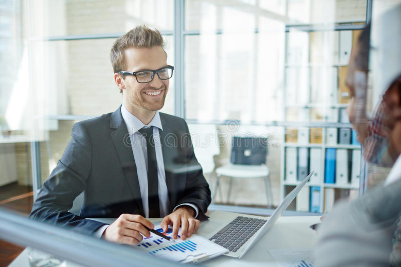 Happy businessman. Happy young businessman looking at his partner during interaction stock images