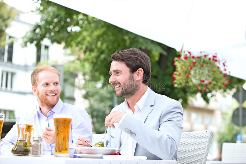 Happy businessmen having food at sidewalk cafe stock photography