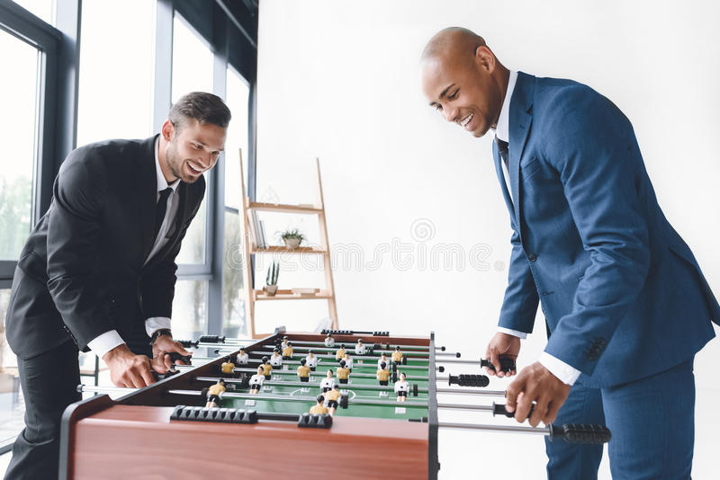Happy businessmen playing table football together royalty free stock photo