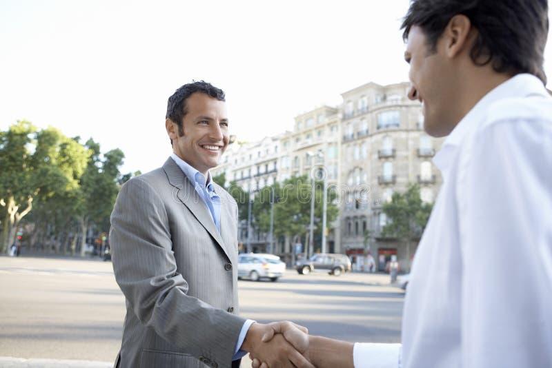 Happy Businessmen Shaking Hands On City Street stock image