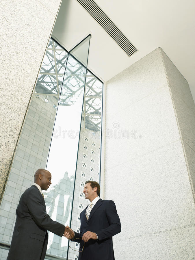 Happy Businessmen Shaking Hands In Office Building stock photography