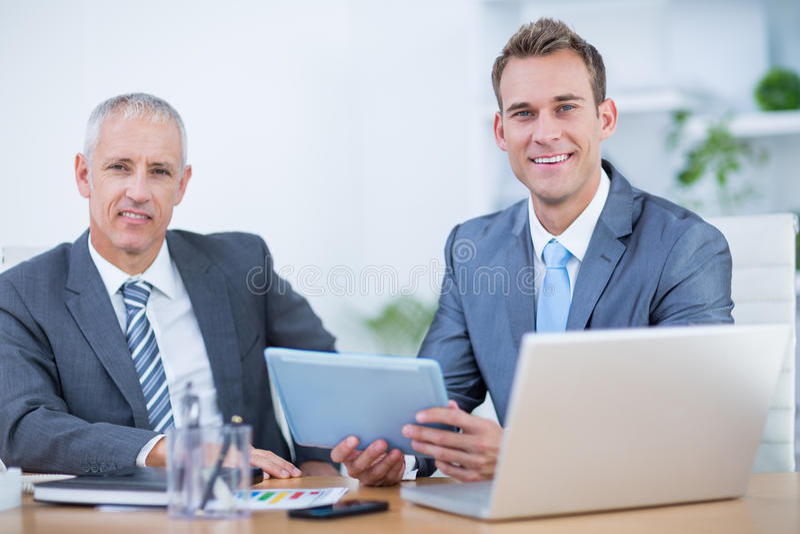 Happy businessmen working together on digital tablet stock photo