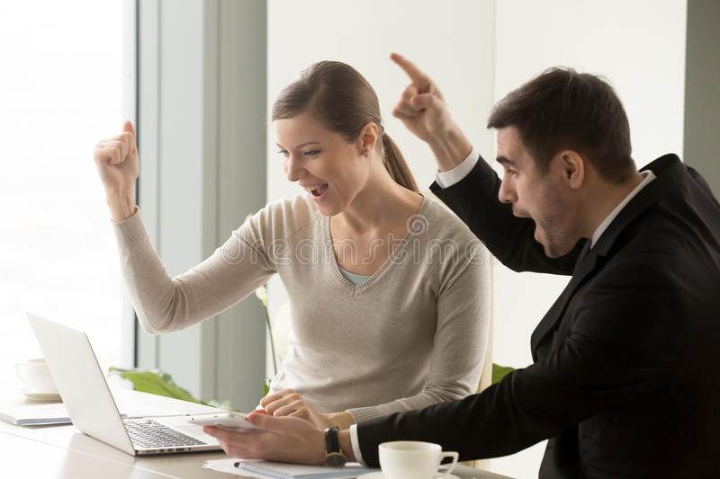 Happy businesspeople celebrating online business success, great. Euphoric happy businesspeople amazed by big win, looking at laptop screen, cheering supporting stock image