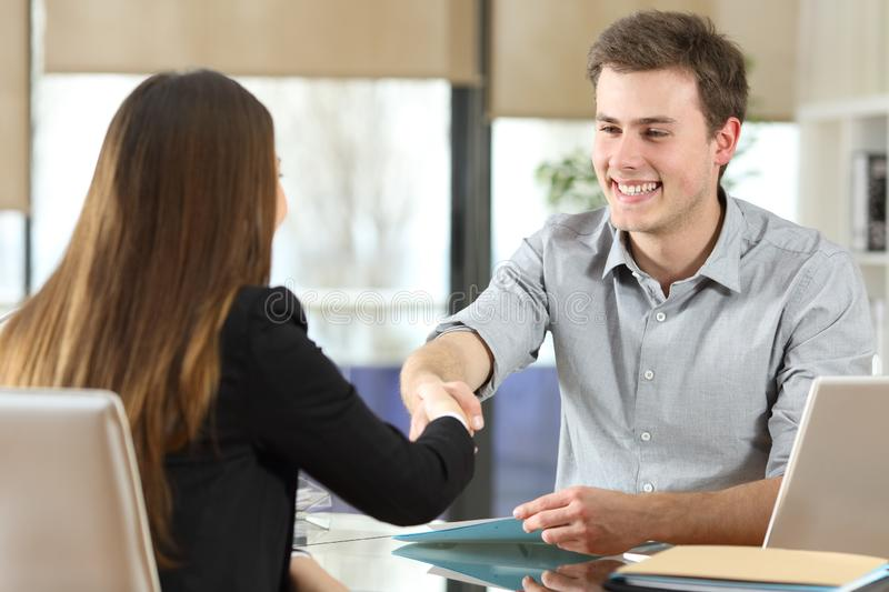 Happy businesspeople handshaking at office stock photo