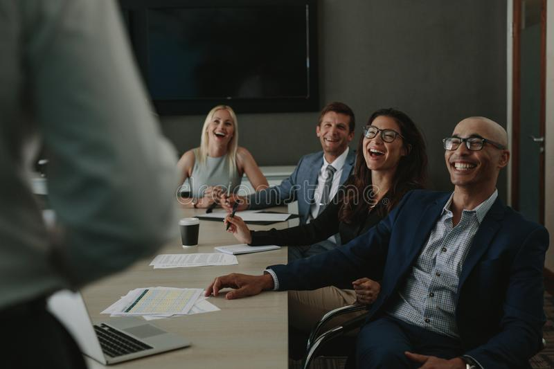 Business people laughing during a conference meeting. Happy businesspeople listening to their colleagues during a staff meeting and laughing. Business men and stock photos